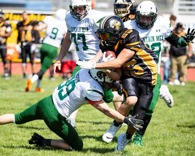 LON AUSTIN/CENTRAL OREGONIAN - Crook County Mountain Men defensive back Damen Hanson makes a tackle on a Rogue Valley Trojan running back during the Mountain Men's 63-0 loss to the Trojans.