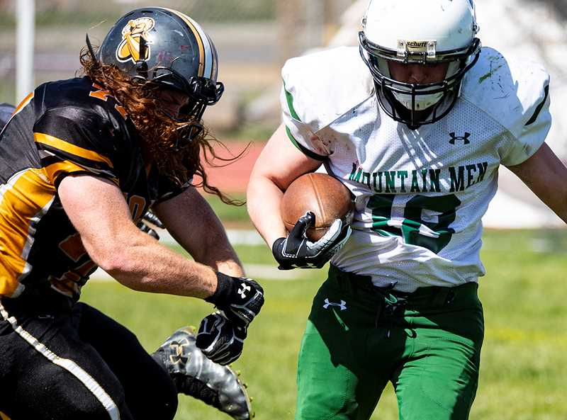 LON AUSTIN/CENTRAL OREGONIAN - Hunter Bourland runs for short yardage during the Mountain Men's loss to Rogue Valley last Saturday.