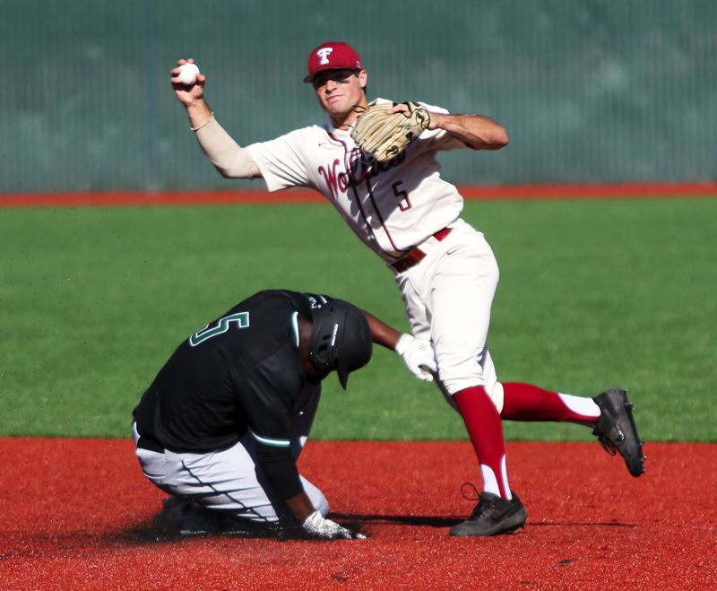 PMG PHOTO: DAN BROOD - Tualatin senior shortstop Kyle Dernedde (right) looks to make a throw to first after forcing out Tigard sophomore Josh Schleichardt at second base.