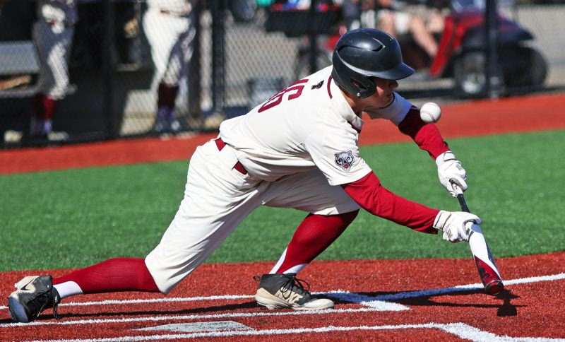 PMG PHOTO: DAN BROOD - Tualatin freshman Griffin Biggs tries to put down a bunt during the Timberwolves' 5-2 win over Tigard on Wednesday.