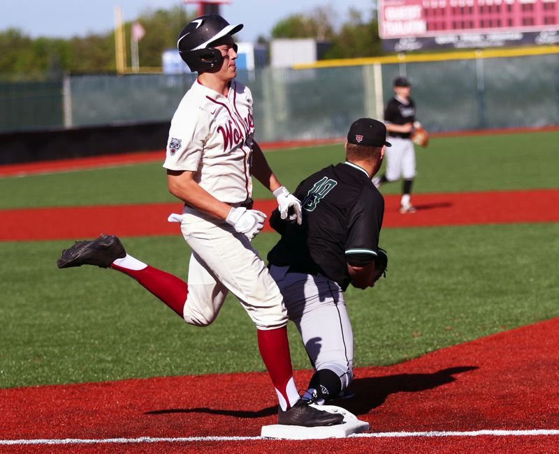 PMG PHOTO: DAN BROOD - Tualatin High School senior Tyler Anderson hits first base during the Wolves' Three Rivers League game with Tigard on Wednesday.