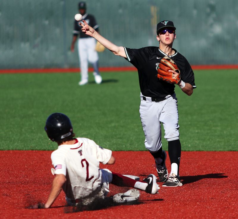 PMG PHOTO: DAN BROOD - Tigard junior shortstop Ethan Clark (right) makes a throw to first after forcing out Tualatin senior Cameron Atkinson during Wednesday's game.
