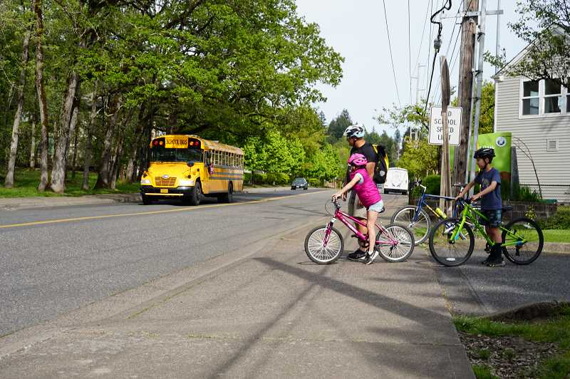 COURTESY PHOTO - The Street Trust member Mike Clark waits with Oak Creek cyclists until it is safe to cross the street.