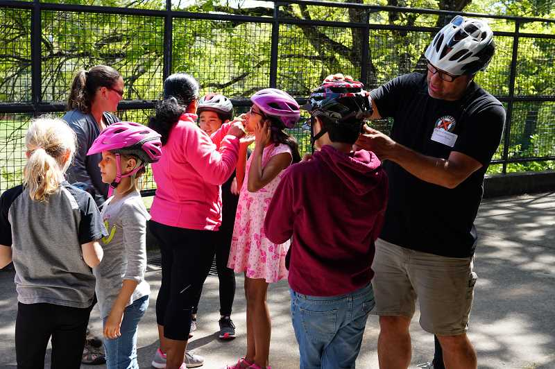 COURTESY PHOTO - Mike Clark (right) of The Street Trust helps Oak Creek students get their helmets fitted correctly.