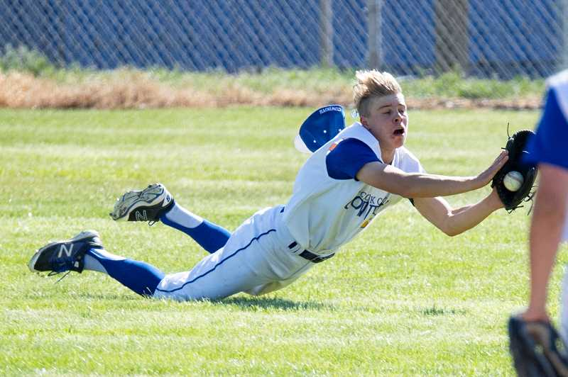 LON AUSTIN/CENTRAL OREGONIAN - Trentyn Maryanski dives to catch a fly ball in right field late in the Cowboys win over Ridgeview in the first game of a doubleheader on Friday. The catch saved at least one run for the Cowboys, who won both games of the doubleheader.