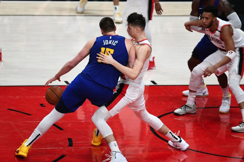 PMG PHOTO: CHRISTOPHER OERTELL - Zach Collins of the Trail Blazers blocks the path of Denver Nuggets center Nikola Jokic from the basket as Evan Turner looks to come help.