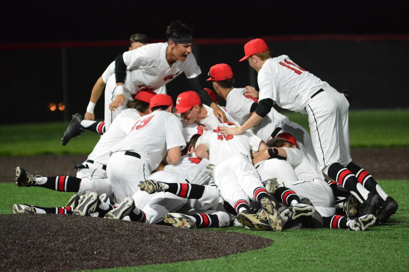 PMG PHOTO: DAVID BALL - Clackamas players dogpile on the mound following the final out in Fridays 8-0 win over Centennial to claim the Cavaliers fourth consecutive Mount Hood Conference title.