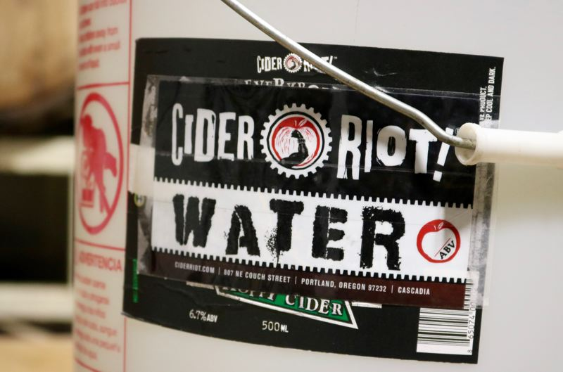 PMG PHOTO: ZANE SPARLING - A water bucket at the Cider Riot! production facility features the cidery's logo.
