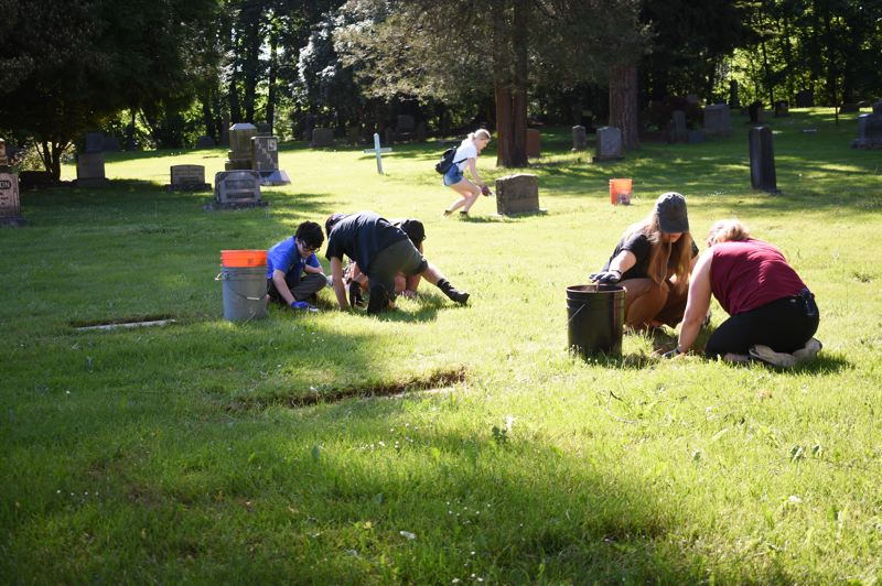 PMG PHOTO: MATT DEBOW - Volunteers pull weeds, and scrape off moss from graves at the Gresham Pioneer Cemetery on Saturday, May 11.