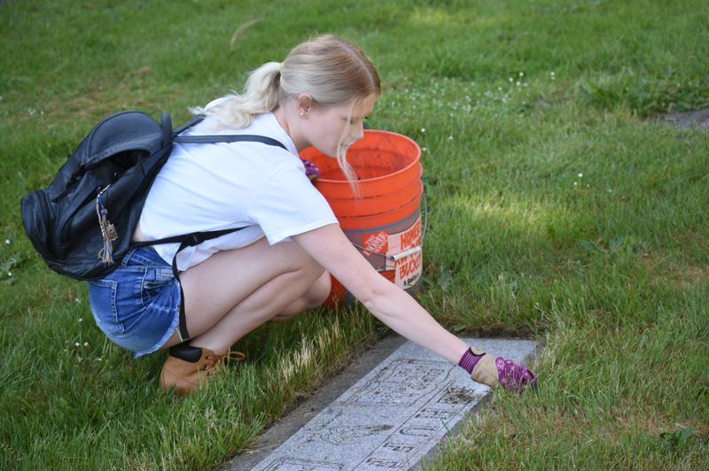PMG PHOTO: MATT DEBOW - Mt. Hood Community College student Zandrea Collins spruces up a grave during the Solve Historic clean-up day on Saturday morning.