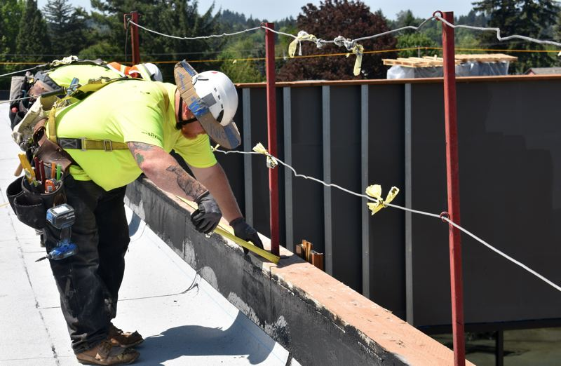 PMG PHOTO: MATT DEBOW  - Nick Woods works on the roof of the new East Gresham Elementary School Friday afternoon.