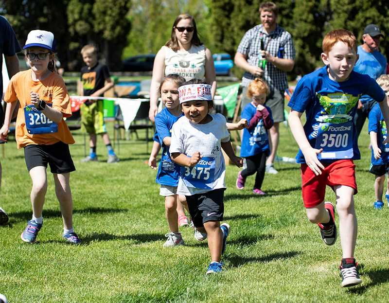 LON AUSTIN/CENTRAL OREGONIAN - A group of enthusiastic kids race away from the starting line during the kids fun run at the Prineville Memorial Hotshot Run, which was held on Saturday in Ochoco Creek Park.
