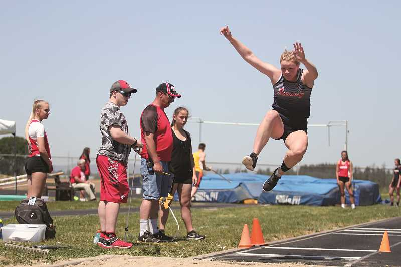 PMG PHOTO: PHIL HAWKINS - Kennedy senior Hallie Sprauer won individual district titles in the long jump (pictured), triple jump and high jump, and was part of the Trojans winning 4x100 relay team.