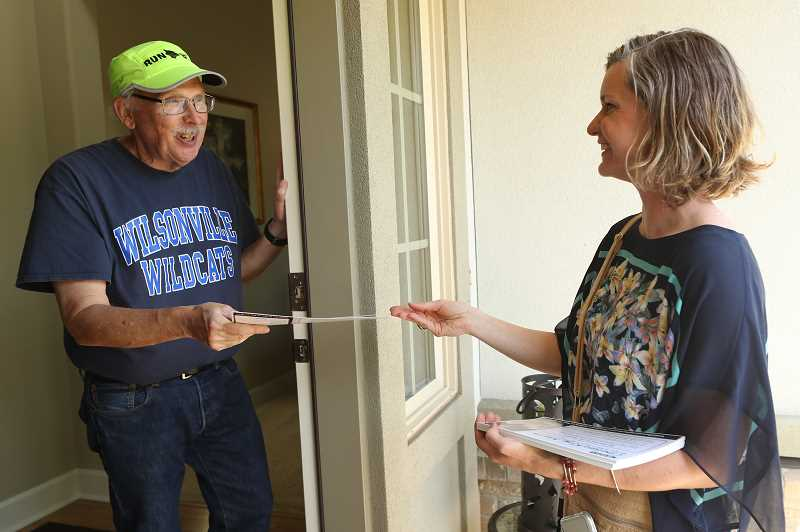 PMG PHOTO: JAIME VALDEZ - Villebois resident Randy Hawley is handed a flyer by West Linn-Wilsonville School Board member Chelsea King Martin who is running for re-election.