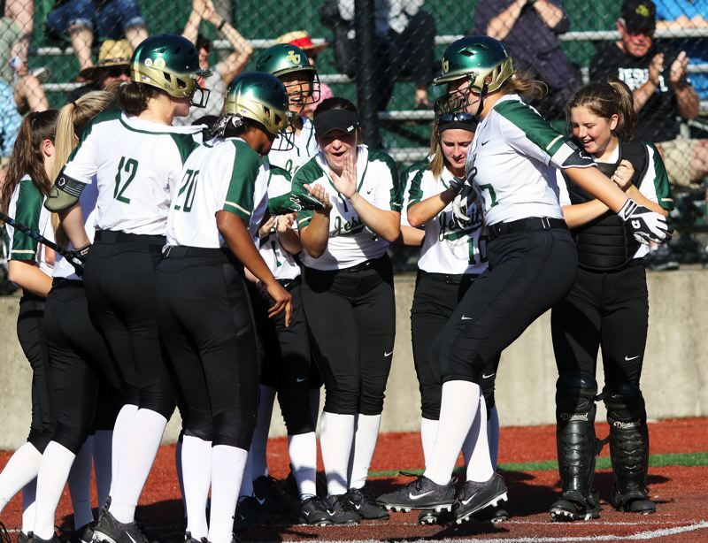 PMG PHOTO: DAN BROOD - Jesuit High School freshman Georgia Corey (right) is greeted at home plate by her Crusader teammates forllowing her two-run home run.