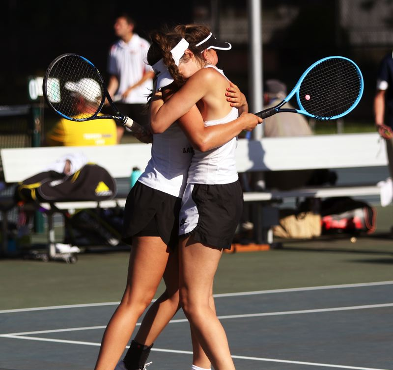 PMG PHOTO: DAN BROOD - Sherwood High School freshman Mandie Jensen (left) and junior Abby Ramer hug following their three-set victory in the Pacific Conference doubles title contest.