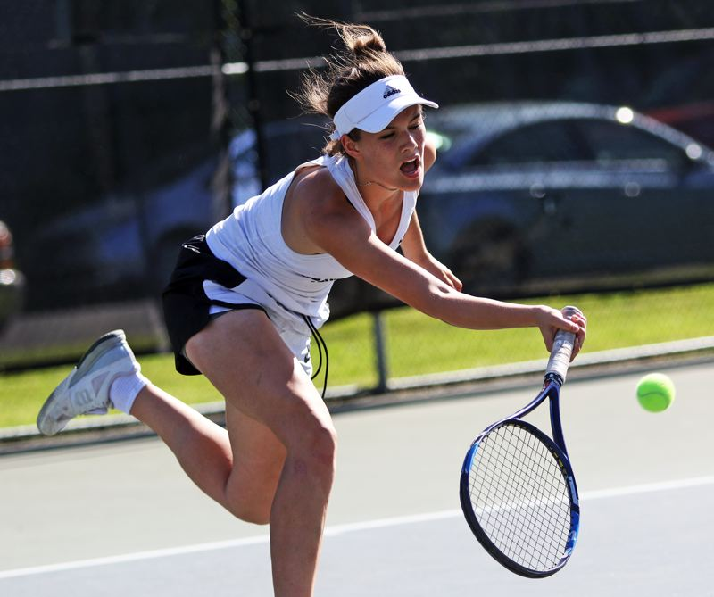 PMG PHOTO: DAN BROOD - Sherwood High School junior Abby Ramer hits a running shot during the girls doubles title match at the Pacific Conference district tournament.