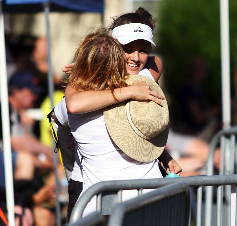 PMG PHOTO: DAN BROOD - Sherwood junior Abby Ramer hugs Lady Bowmen head coach Roxanne Imbrie following the girls doubles championship match at the Pacific Conference district tournament.