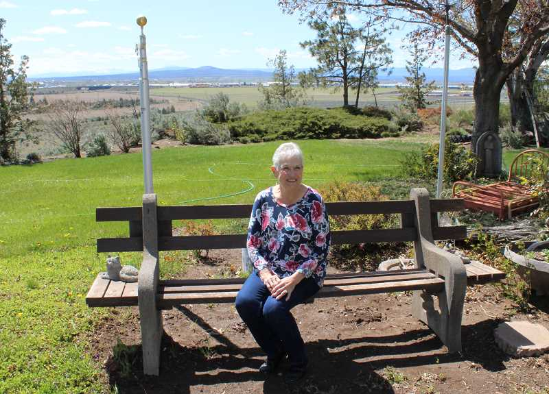 JENNIFFER GRANT/MADRAS PIONEER - Helen Houts, who has been named the grand marshal of the Jefferson County Fair and Rodeo, sits on a conccrete and wood bench made by her husband's father. Helen and Bill Houts moved to Madras in 1960 to farm, as part of the Houts and Sons family farm.