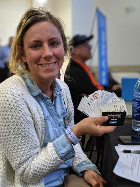 PMG PHOTO: JOSEPH GALLIVAN - Chelsea Moe the store personnel clerk at WinCo at 182nd and Powell,  looks through some of the business cards she received from talking to more than 50 people at the over 50s job fair.