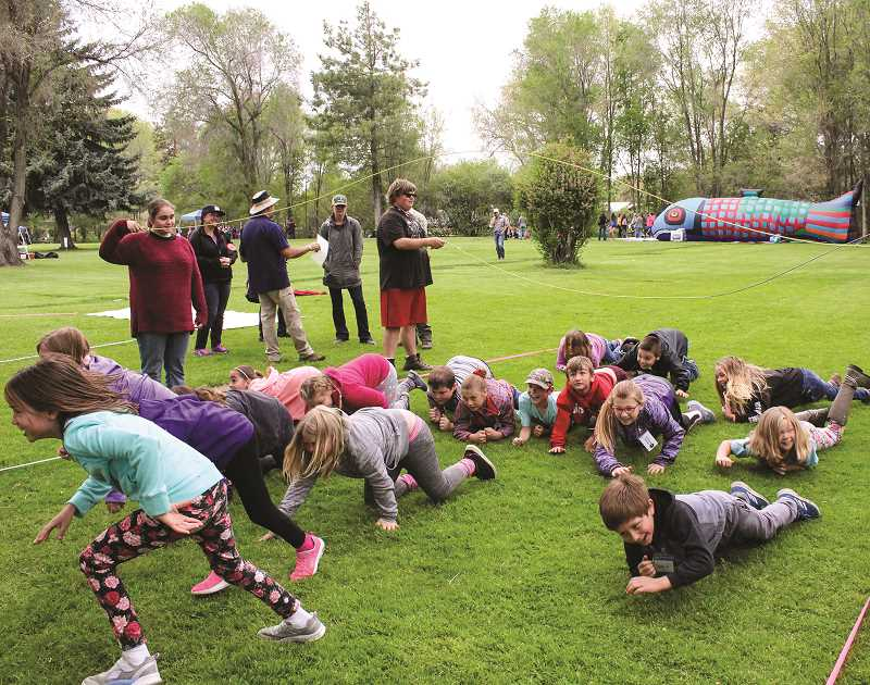 JASON CHANEY/CENTRAL OREGONIAN  - Marissa Stafford's third-grade Crooked River Elementary class dodges jump ropes and more as they receive a lesson about the salmon life cycle and the treacherous journey upstream to spawn.