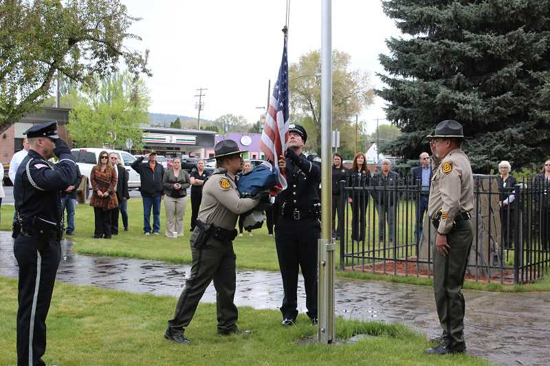 JASON CHANEY - Local law enforcement officials lower the flag in front of the Crook County Courthouse in honor of those officers who have died in the line of duty.