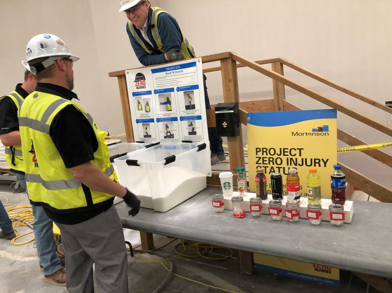 COURTESY:  JULIA SHOLIAN/AMERICAN HEART ASSOCIATION - Workers at a local construction job site participate in a Rethink Your Drink activity designed to show the amount of sugar in energy drinks, soda and other beverages