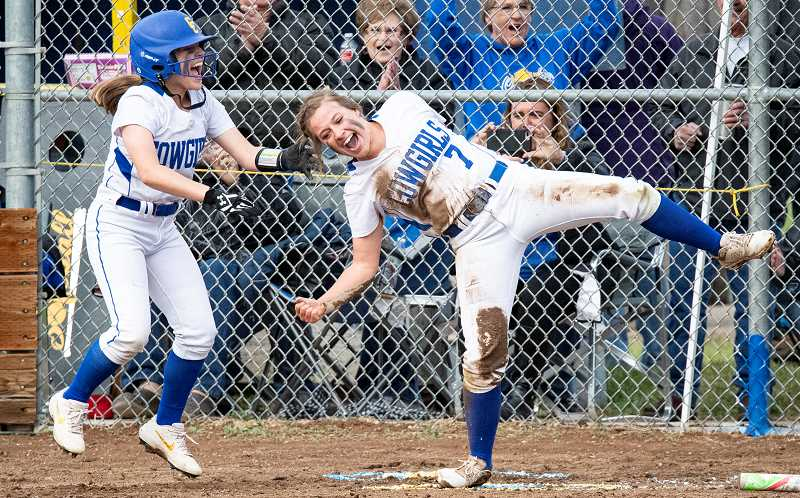 LON AUSTIN/CENTRAL OREGONIAN - Mikinley Puckett, left, and Ashley Owens celebrate after Owens scored the winning run against Redmond on Tuesday. It was senior night for the Cowgirls, who earned a 14-13 win by scoring three runs in the bottom half of the seventh inning.