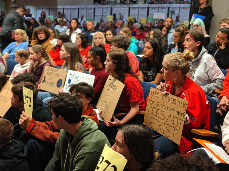 PMG PHOTO: COURTNEY VAUGHN - Students fill the seats in the auditorim of the Blanchard Education Service District building holding signs urging the board to fully implement a climate change education resolution that was adopted in 2016.