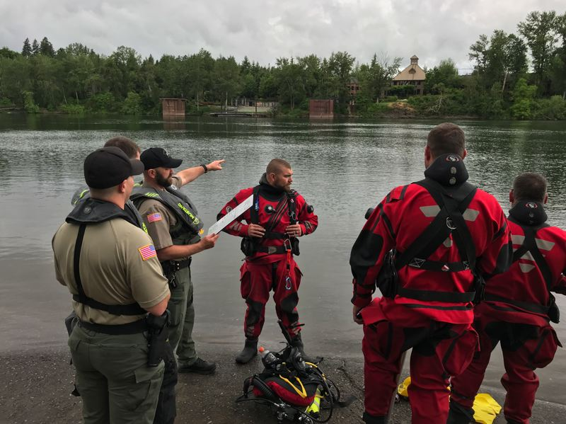 CCSO PHOTO - Clackamas County Sheriff's search and rescue divers coordinate a plan to remove a car from the Willamette River near the Oak Grove Boat Ramp.