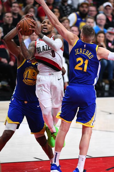 PMG PHOTO: CHRISTOPHER OERTELL - Trail Blazers guard Damian Lillard is met by two Golden State defenders on his way to the basket in Game 3 Saturday night at Moda Center.