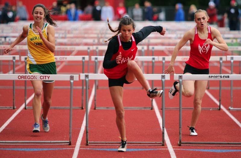 PMG PHOTO: JIM BESEDA - Oregon City's Harley Daniel (center) won the girls 100-meter hurdles in 15.33 seconds and Alexis Pearson (right) was second in 15.88 at Friday's Three Rivers League track and field championships.