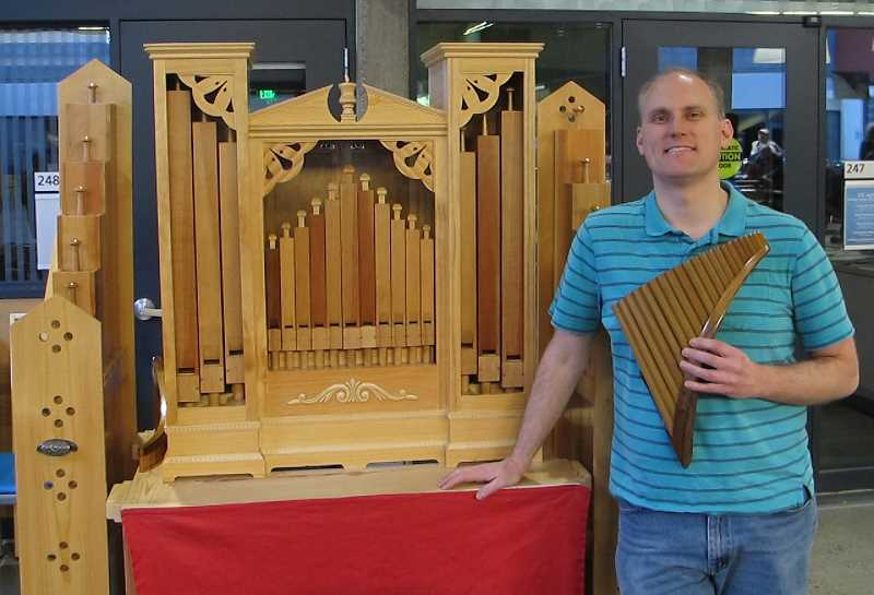 PMG PHOTOS: BILL GALLAGHER - Sean Koreski standing next to the $20,000 putative wooden organ he made by hand, while holding one of the pan flutes he also made.