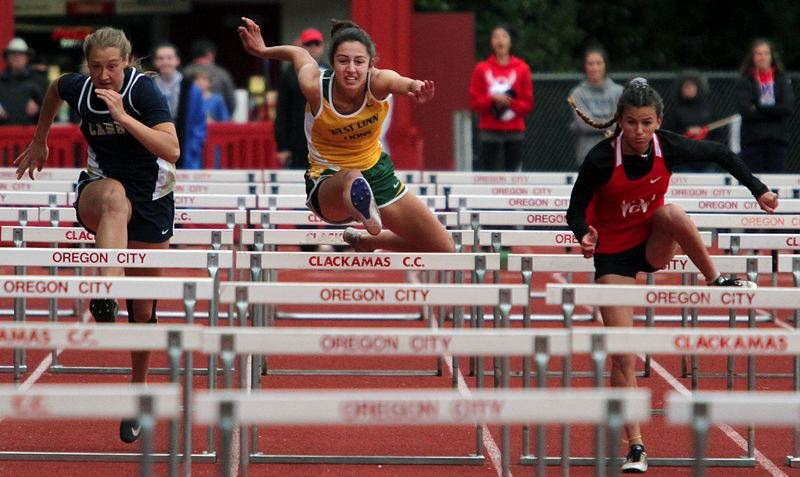 PMG PHOTO: MILES VANCE - West Linn senior Sophie Conrad races to fourth place in the 100-meter high hurdles during the Three Rivers League district track meet at Oregon City's Pioneer Memorial Stadium on Friday, May 17.
