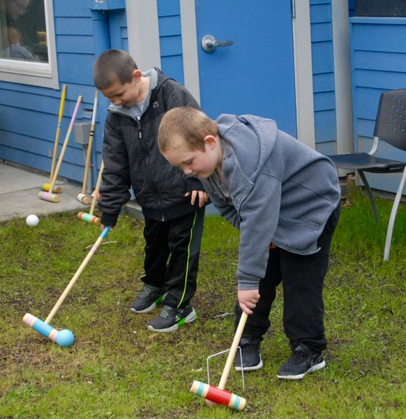 PMG PHOTO: MATT DEBOW - Adrien Sanchez-Urcino, 5, plays croquet with Jaden Corn, 6, at the reopening celebration.
