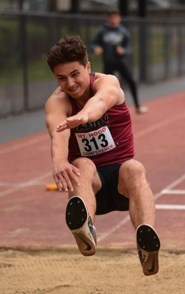 PMG PHOTO: DAVID BALL - Sandy senior Glynne McGaughey flies into the sand during his runner-up finish in the long jump, coming up less than two inches short of the win.