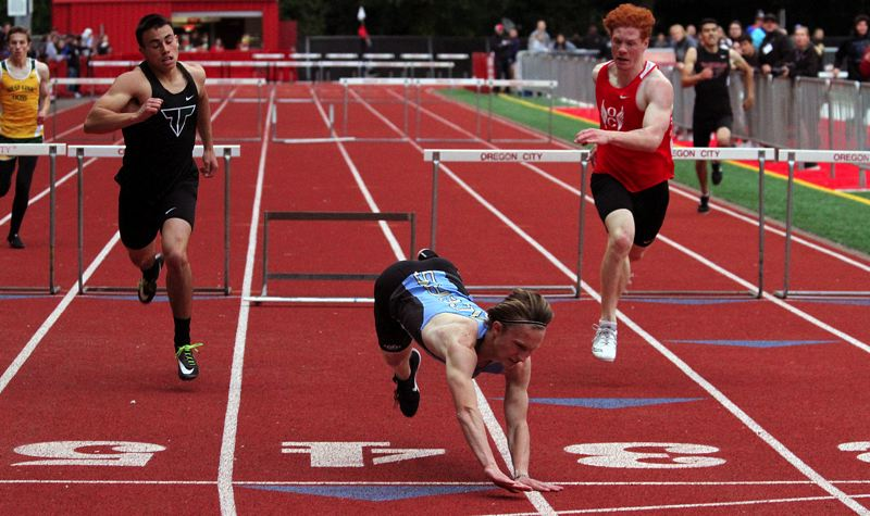 PMG PHOTO: MILES VANCE - Lakeridge's Luke Neville tumbles across the finish line while winning the 300-meter intermediate hurdles at the Three Rivers League district track meet at Oregon City's Pioneer Memorial Stadium on Friday, May 17.