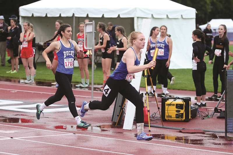 PMG PHOTO: JUSTIN MUCH - St. Paul's Isabelle Wyss receives the baton handoff from Rachel Vela as 4x400 teammates Sadie Smith and Taysha Veeman look on in the background in the final event of the 2019 1A Track and Field State Championship on Saturday at Western Oregon University.