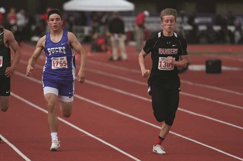 PMG PHOTO: PHIL HAWKINS - St. Paul junior Gianni Grasso finished third in the 100-meter dash finals at the 1A State Track and Field Championships on Saturday, behind Dufur's Asa Farrell and Tanner Masterson (right).