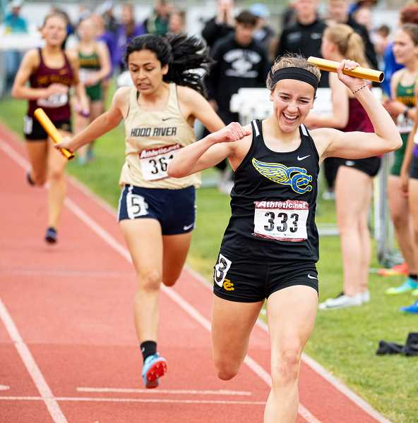 LON AUSTIN/CENTRAL OREGONIAN - Maggie Ramoss celebrates as she crosses the finish line in first place in the 4x400 relay race. Ramoss, Alyson Thomas, Gracie Kasberger and Mckinzee Mode finished with a time of 4:13.69, seven seconds faster than the Cowgirls have run all season.