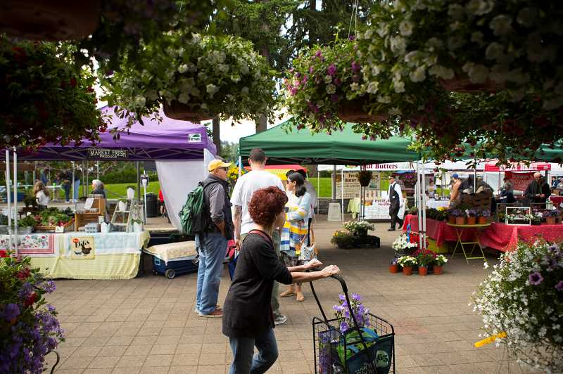 PMG PHOTO: JAIME VALDEZ - Folks walk by hanging plants from Stoller Farms on the opening day of the Lake Oswego Farmers' Market at Millennium Plaza Park.