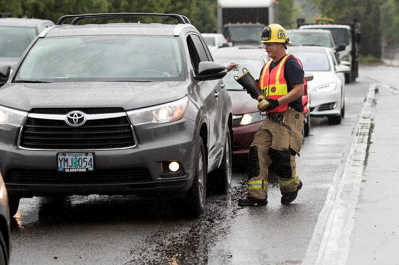 PMG PHOTO: JAIME VALDEZ - Jeff Ross, a firefighter with Tualatin Valley Fire & Rescue at Station 51, collects money for the Muscular Dystrophy Association during a Fill the Boot event at the intersection of Southwest Boones Ferry and Wilsonville roads.