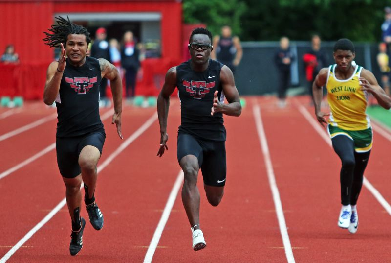 PMG PHOTO: DAN BROOD - Tualatin High School senior Kwabena Lynn (center) ran to victory, while fellow Timberwolf senior Dominique Loggins (left) took second place in the 100-meter dash at the TRL district meet.