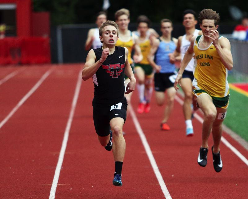 PMG PHOTO: DAN BROOD - Tualatin junior Andrew Payton (left) sprinted past West Linn's Kenney McElroy at the finish to win the 800-meter run. Payton also won a district title in the 1,500.