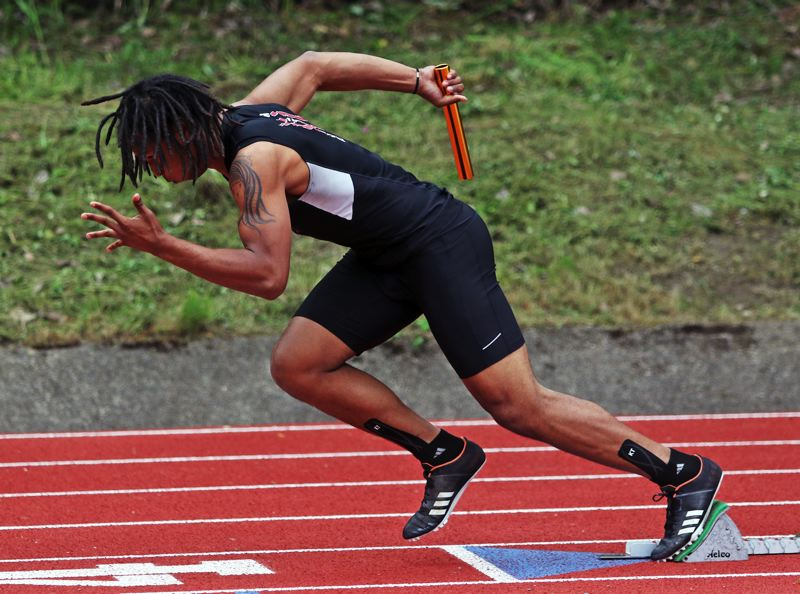 PMG PHOTO: DAN BROOD - Tualatin High School senior Dominique Loggins takes off in the 4 x 100 relay at the Three Rivers League district track and field championships.