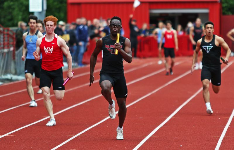 PMG PHOTO: DAN BROOD - Tualatin High School senior Kwabena Lynn (center) nears the finish line in the 4 x 100 relay at the Three Rivers League district meet.