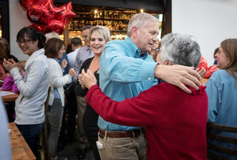 PMG PHOTO: JONATHAN HOUSE - John Wallin celebrates with supporters after learning that he won reelection to the Lake Oswego School Board.