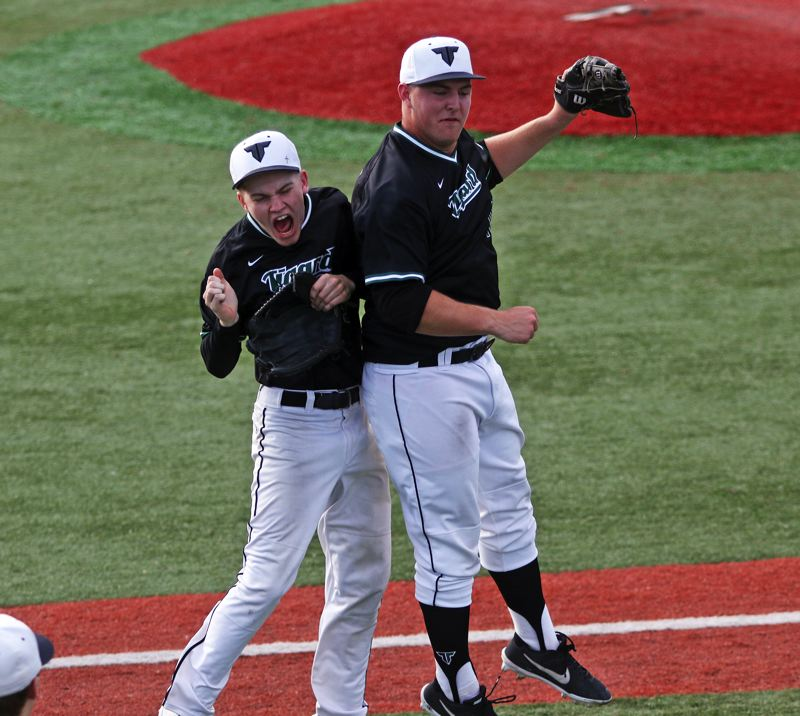 PMG PHOTO: DAN BROOD - Tigard High School seniors C.J. Rivers (right) and Sam Gerkman celebrate following the Tigers' come-from-behind 7-6 win over South Medford in Monday's state playoff game.