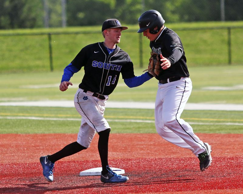 PMG PHOTO: DAN BROOD - Tigard High School senior Cameron Laroche (right) is tagged out by South Medford shortstop Zach Ankeny during Monday's state playoff game.