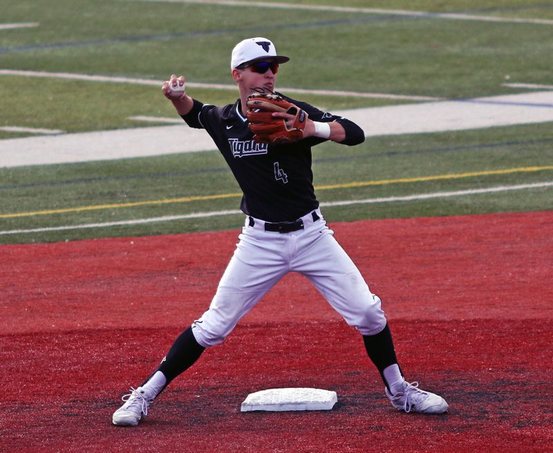 PMG PHOTO: DAN BROOD - Tigard High School junior shortstop Ethan Clark gets ready to make a throw to first base to complete a game-ending double play during the Tigers' 7-6 playoff win over South Medford.